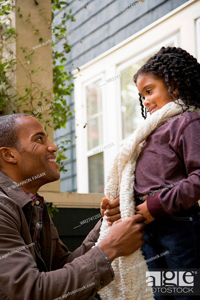 Stock Photo: Father tying daughters scarf.