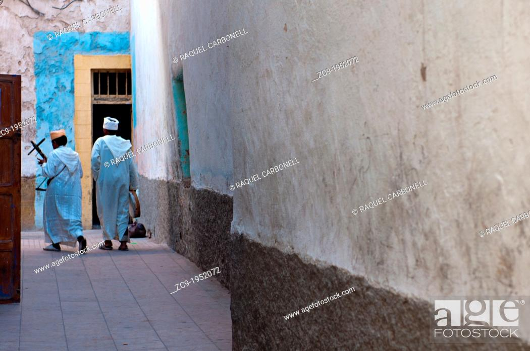 Stock Photo: Traditional musicians walking by an alleyway in Essaouira medina, Morocco.