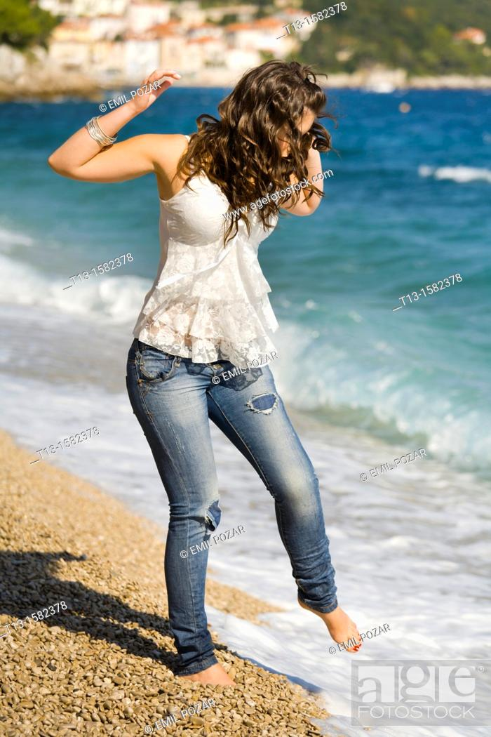 Stock Photo: Attractive young woman is testing water with a bare foot.