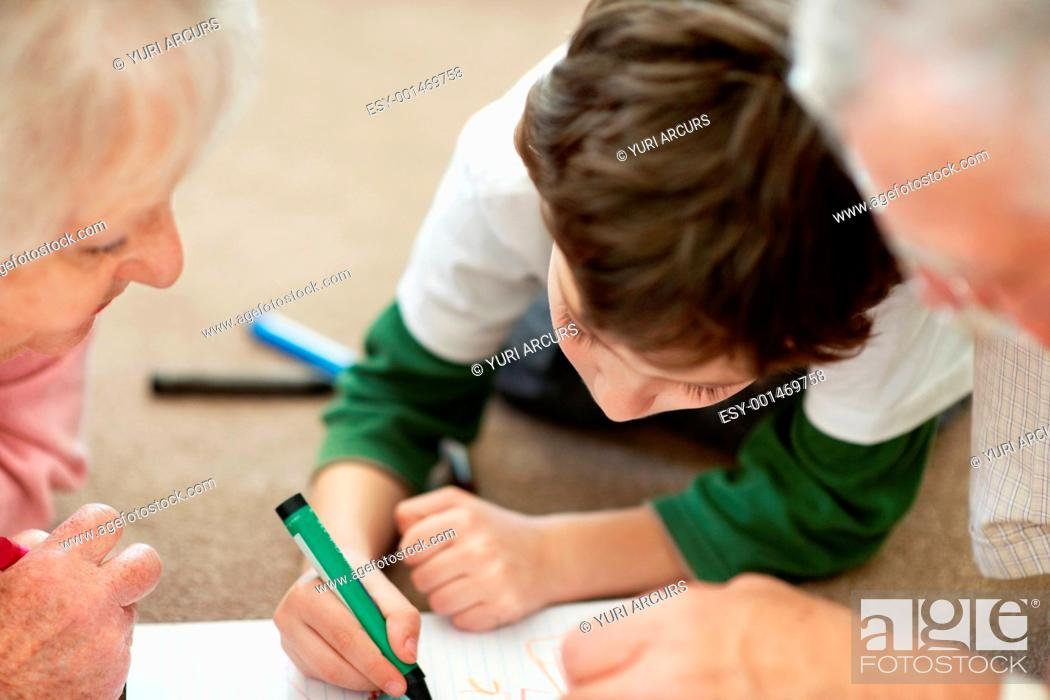 Stock Photo: Adorable little boy making a drawing with his grandparents while lying on floor.
