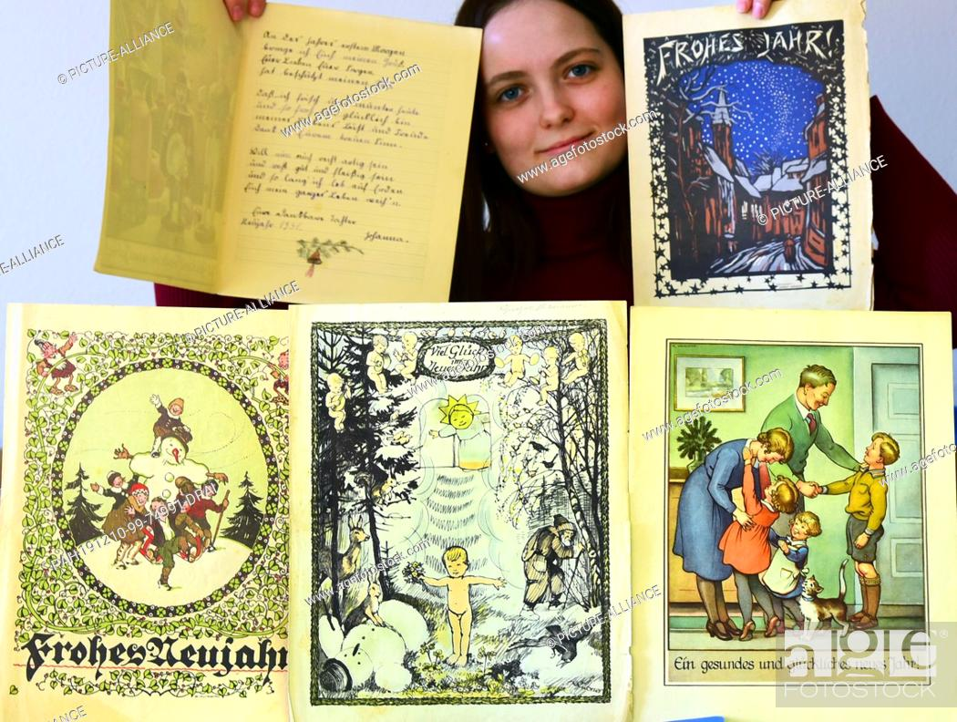 Stock Photo: 06 December 2019, Saxony, Delitzsch: In the Museum Barockschloss Delitzsch, staff member Mania Kurrey shows cards with New Year's wishes from the years.