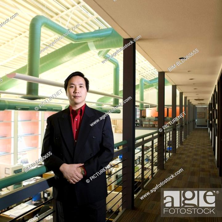 Stock Photo: Asian businessman leaning on railing.