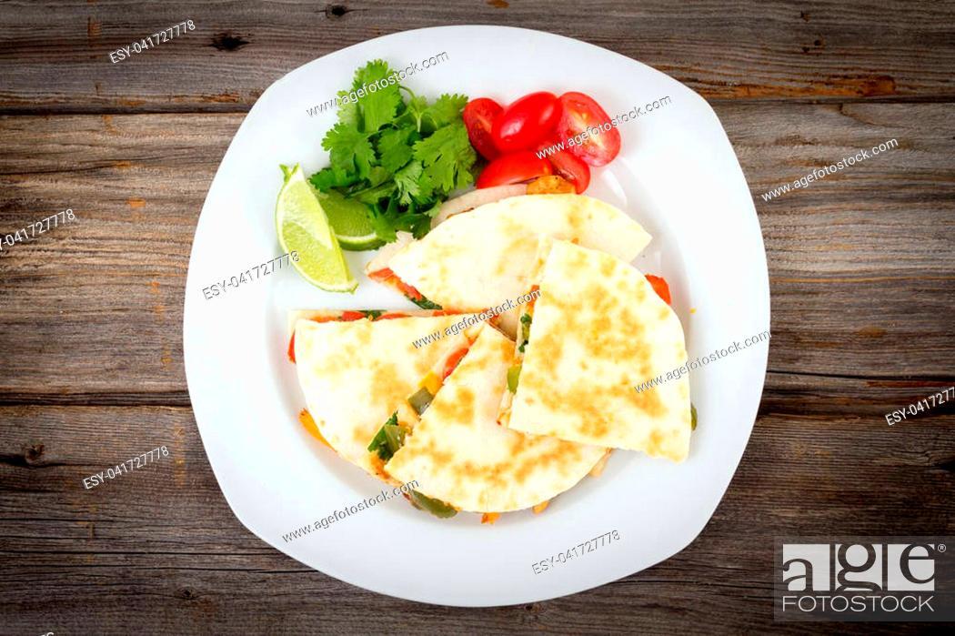 Photo de stock: Chicken quesadilla dish on wooden rustic table.