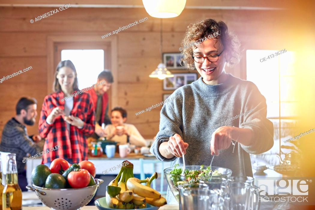 Stock Photo: Woman tossing salad for friends in cabin.