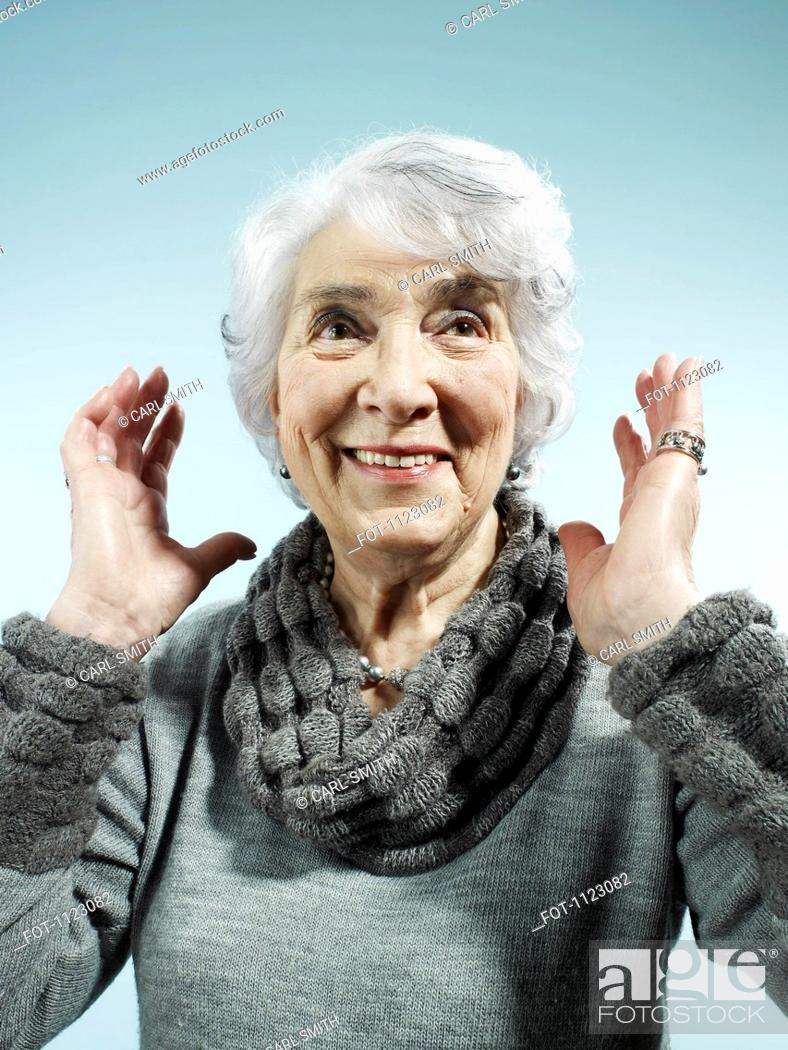 Stock Photo: A senior woman with her arms raised in surprise.
