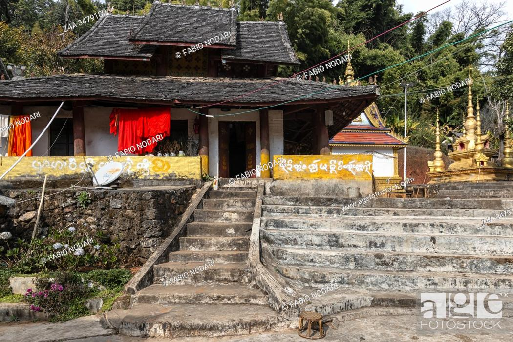 Stock Photo: Xishuangbanna, China - December 31, 2019: Dai temple in the countryside of Xishuangbanna. Foreing text saying: Buddhist temple.