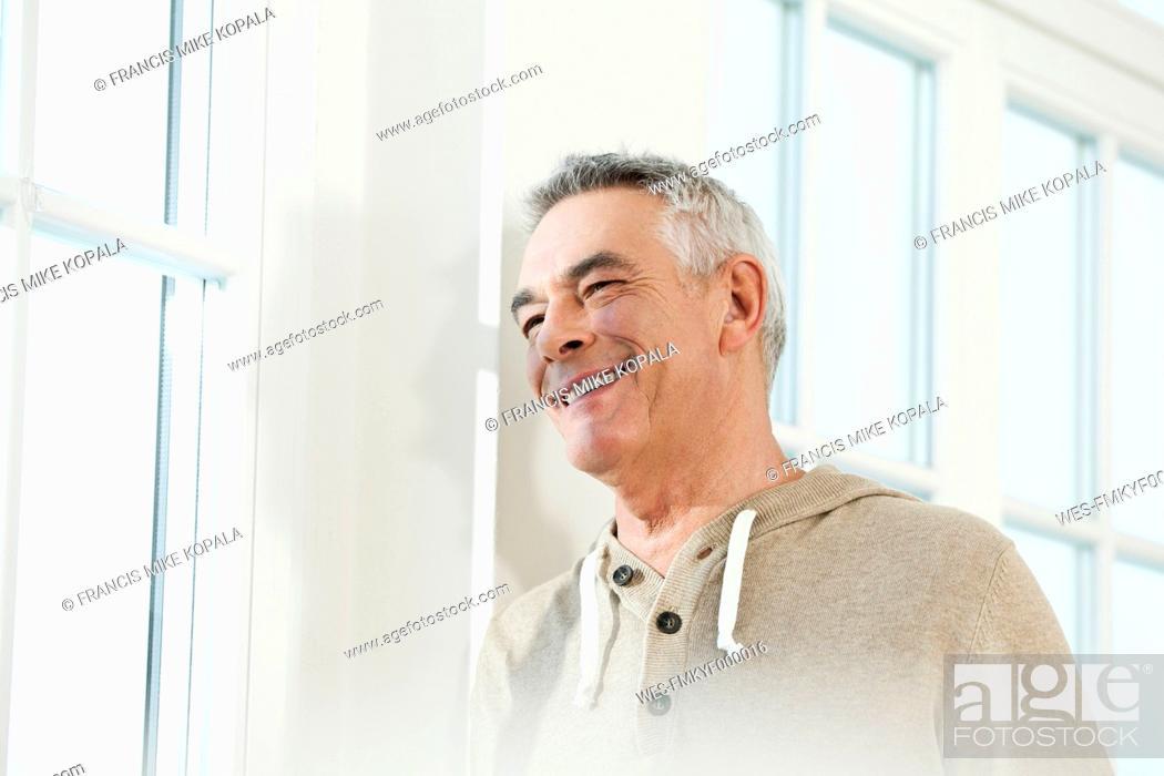Stock Photo: Germany, Berlin, Senior man looking away, smiling.