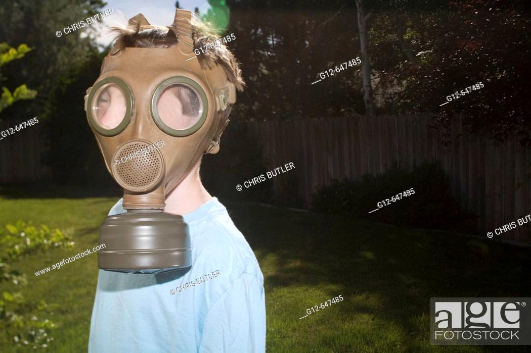 Stock Photo: Boy, age 7, wears vintage military gas mask.