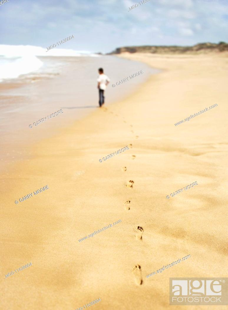 Stock Photo: Boy walking along sandy beach back view.