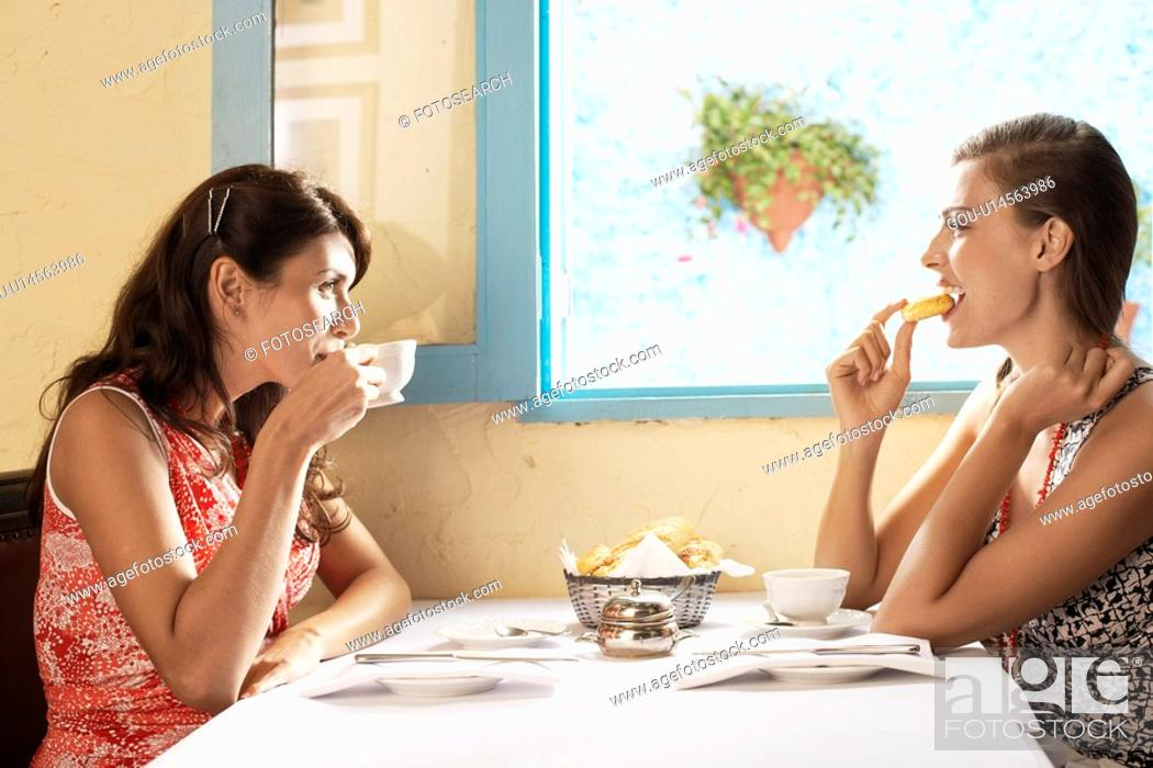 Stock Photo: Two women eating and drinking in restaurant.