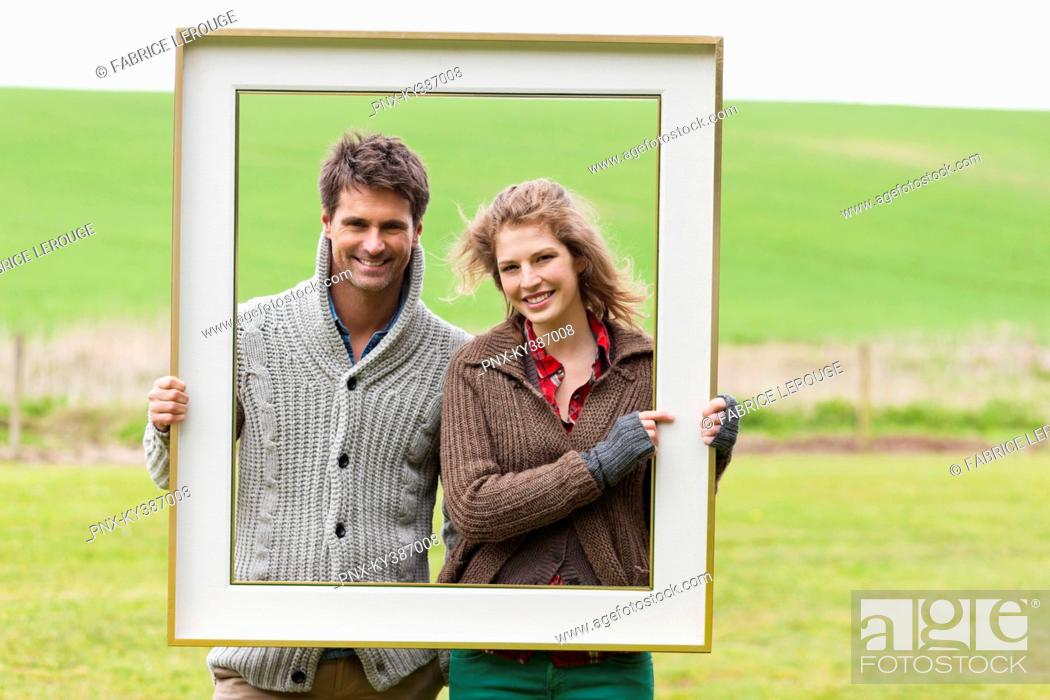 Stock Photo: Portrait of a couple holding a frame in a field.