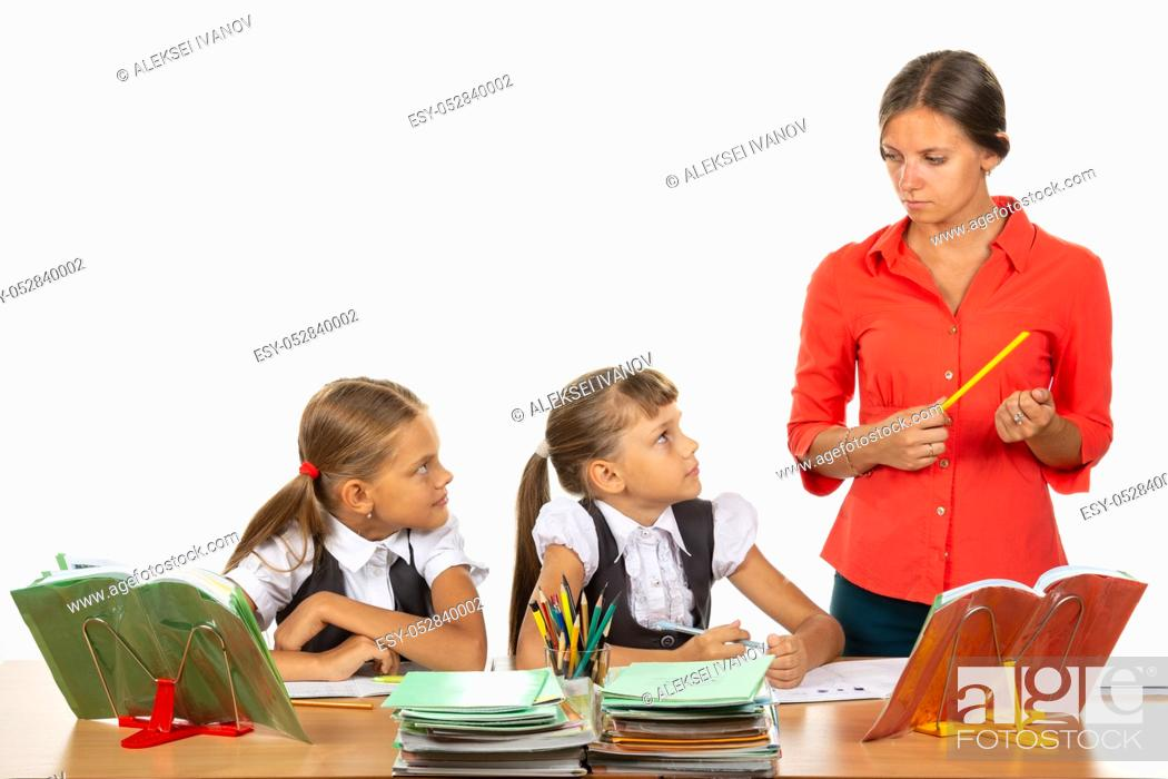 Stock Photo: Children at their desks look at the angry teacher with fear.