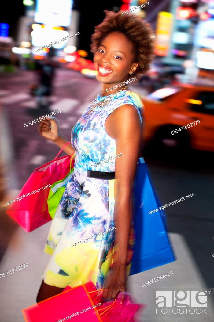 Stock Photo: Woman carrying shopping bags on city street.