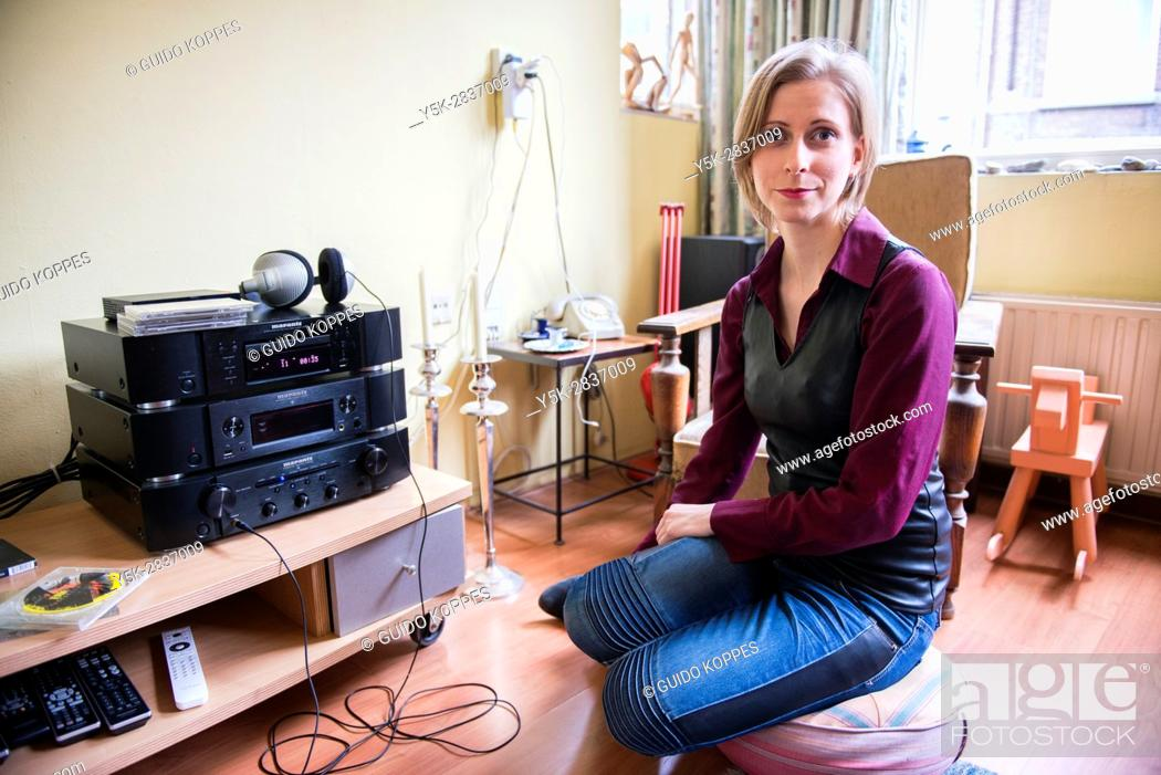 Imagen: Tilburg, Netherlands. Young adult caucasian woman enjoying music from her stereo hifi set using a headset and a cd or compact disc.