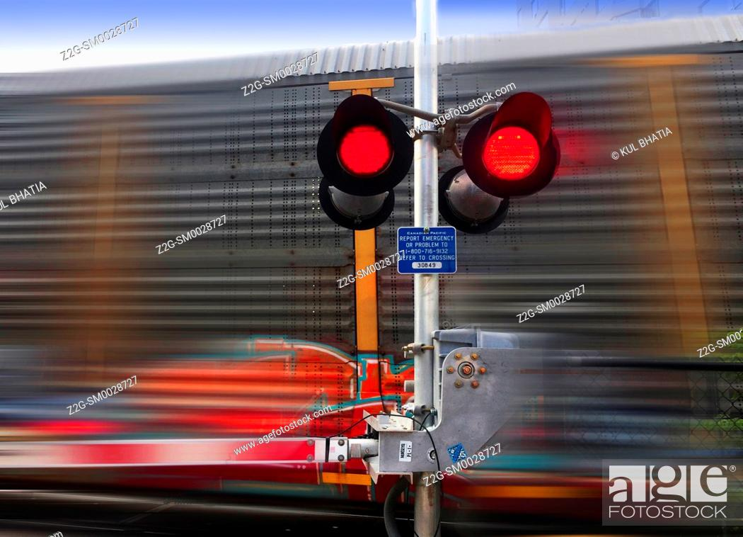 Stock Photo: A train speeds past a railway crossing barrier, red lights flickering, Ontario, Canada.
