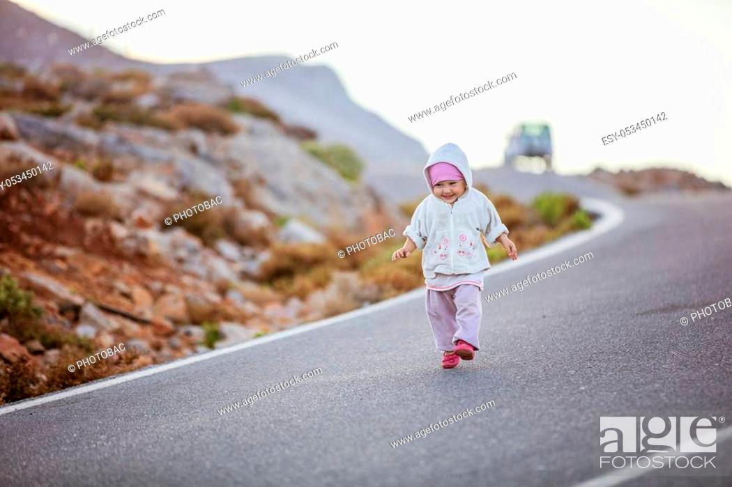 Stock Photo: Happy little girl running down road. Parents' car parked along road in distance.
