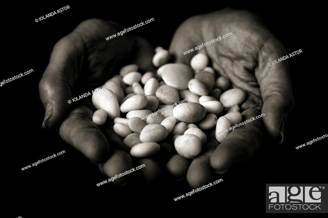 Stock Photo: Hands that offer white stones, polished  Means the whisper of water  Conceptual  Black and white.