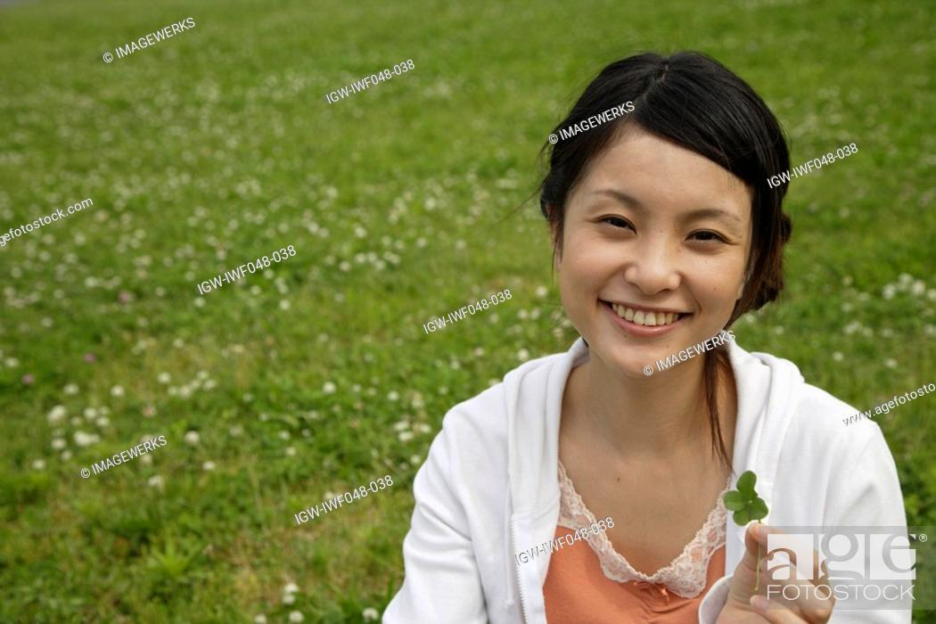 Stock Photo: Portrait of a young woman holding a plant.