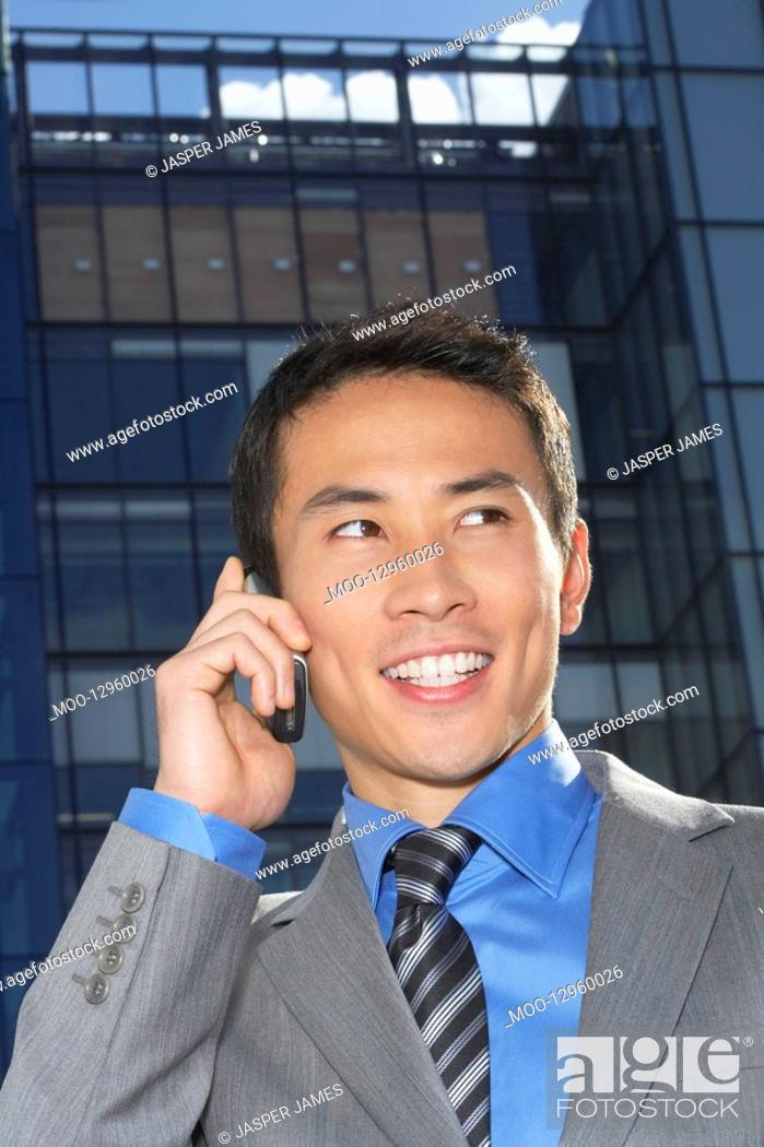 Stock Photo: Smiling Businessman Using Cell Phone outside building.