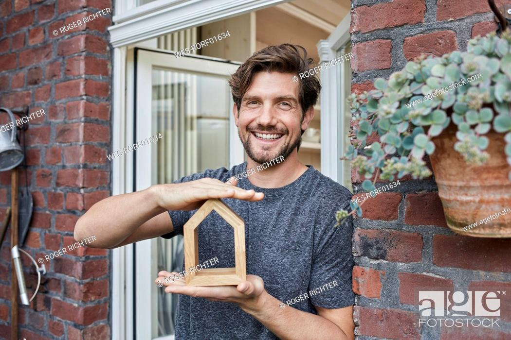 Stock Photo: Portrait of smiling man at house entrance holding house model.