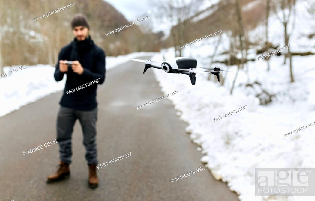 Stock Photo: Spain, Asturias, man navigating a drone in the snowy mountains.