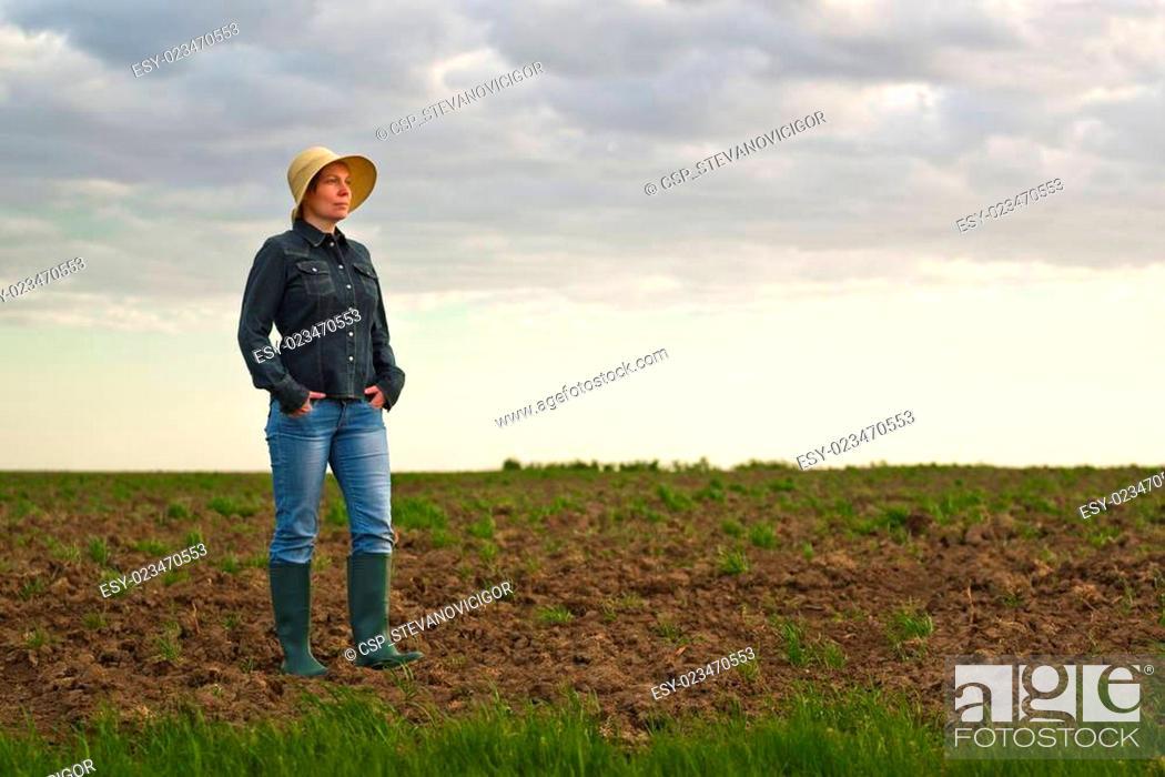 Stock Photo: Female Farmer Standing on Fertile Agricultural Farm Land Soil.