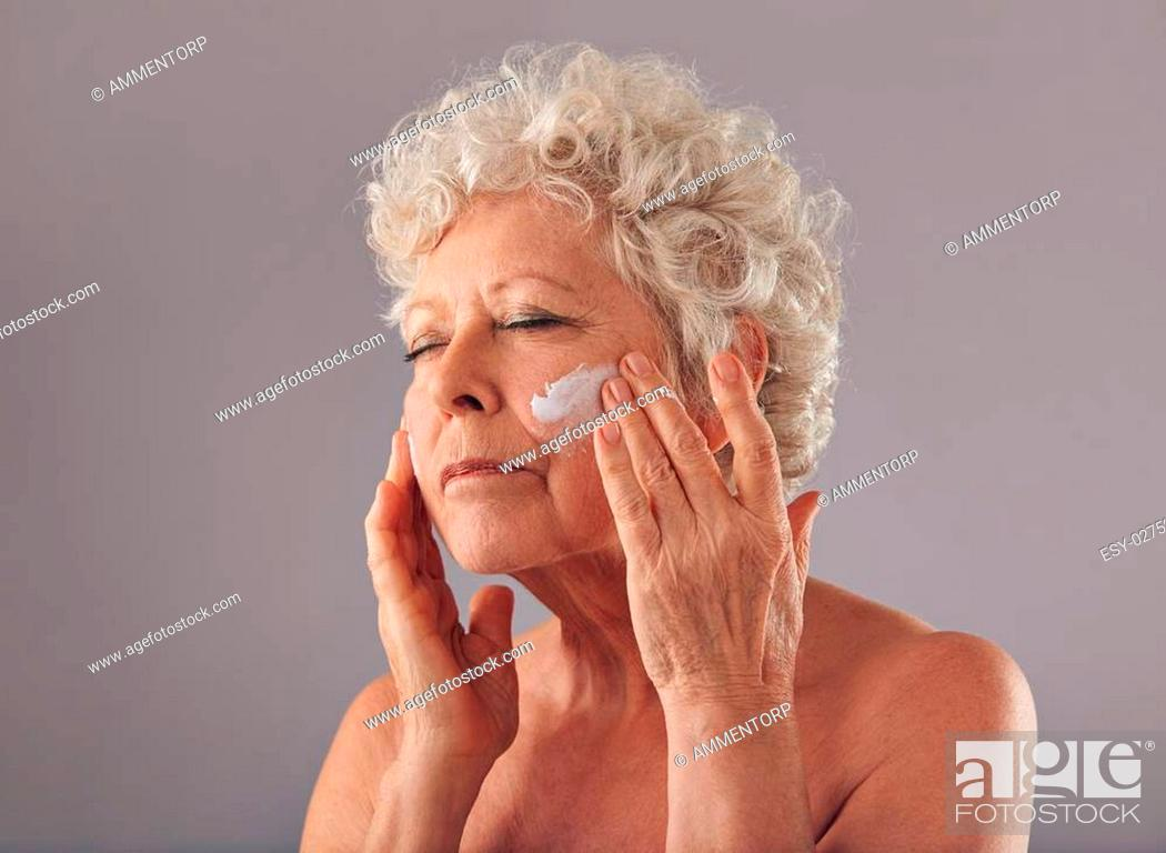 Stock Photo: Portrait of senior woman putting on anti-aging cream on her face against grey background. Anti-ageing concept, woman in her 70s applying skin cream on her face.