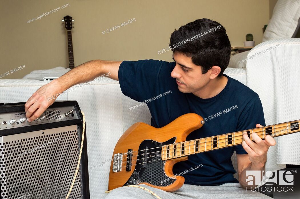 Imagen: Man adjusting amplifier to play electric bass sitting at home.