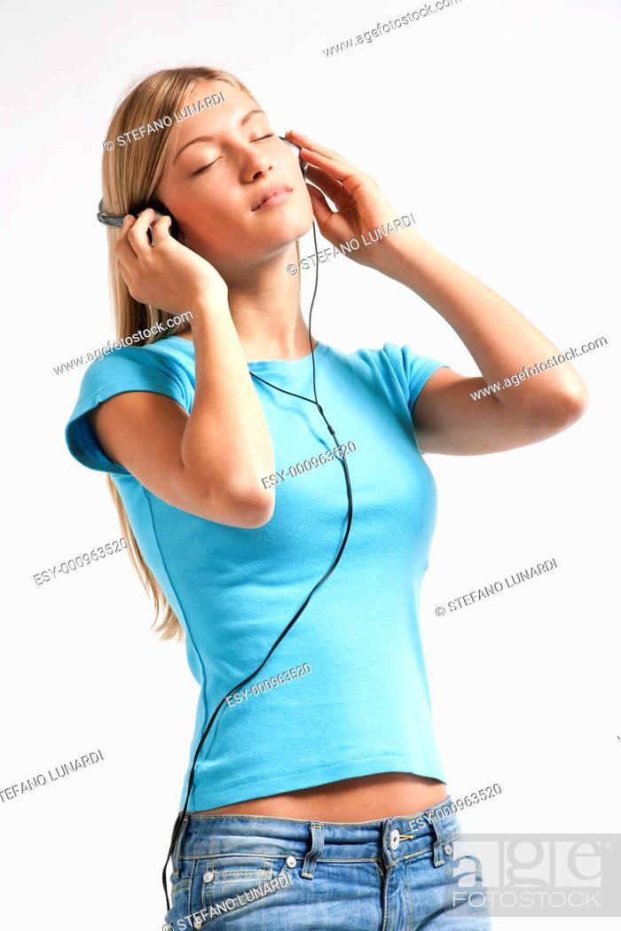 Stock Photo: Teenage girl listening to the music, isolated on white.