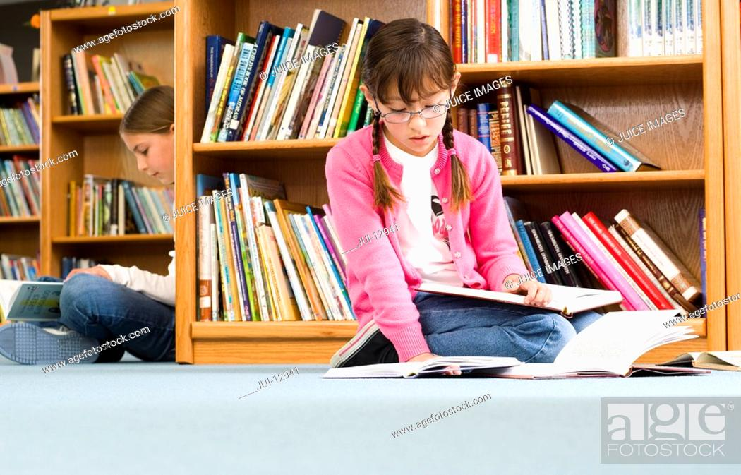 Stock Photo: Girl 9-11 and friend reading in library.