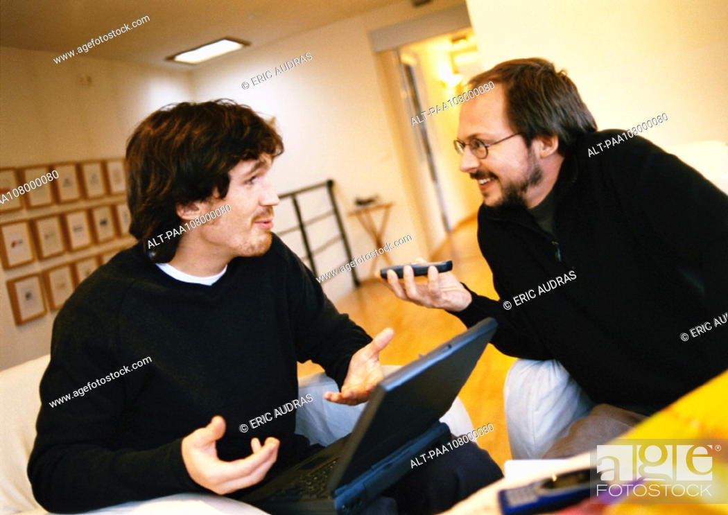 Stock Photo: Men talking, one with laptop computer.