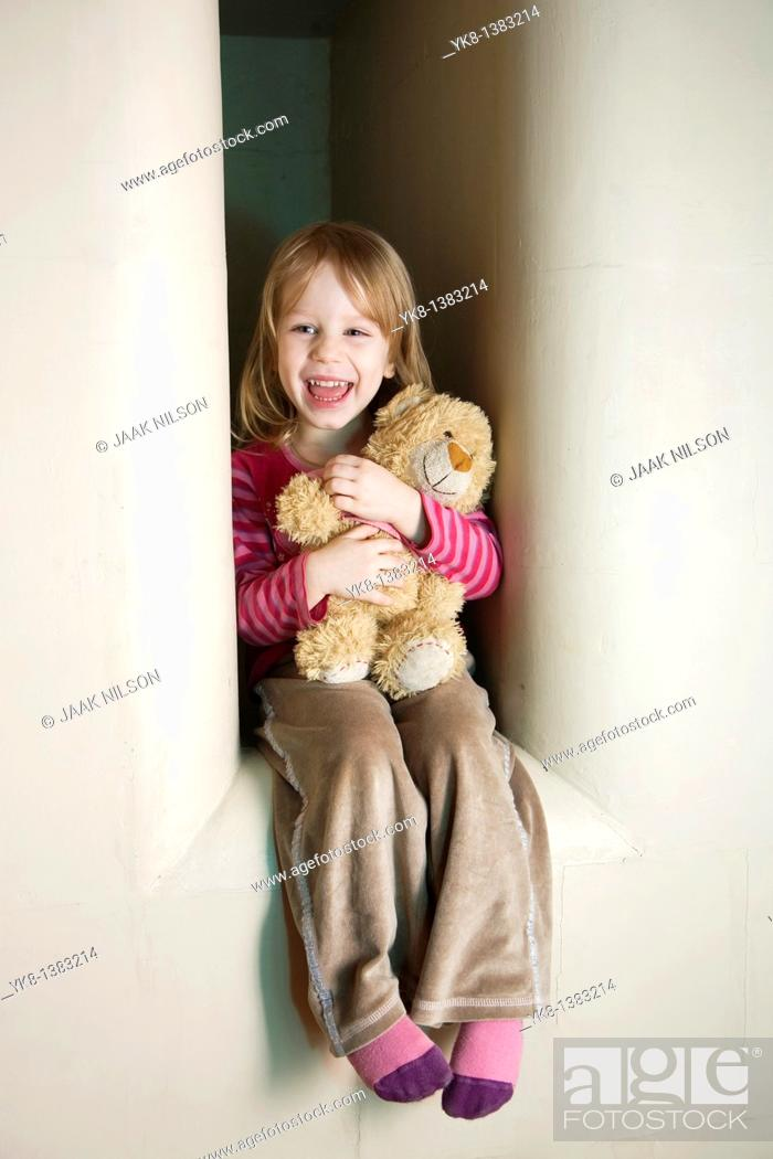Stock Photo: Three Year Old Girl Sitting in Stove Recess With Teddy Bear.