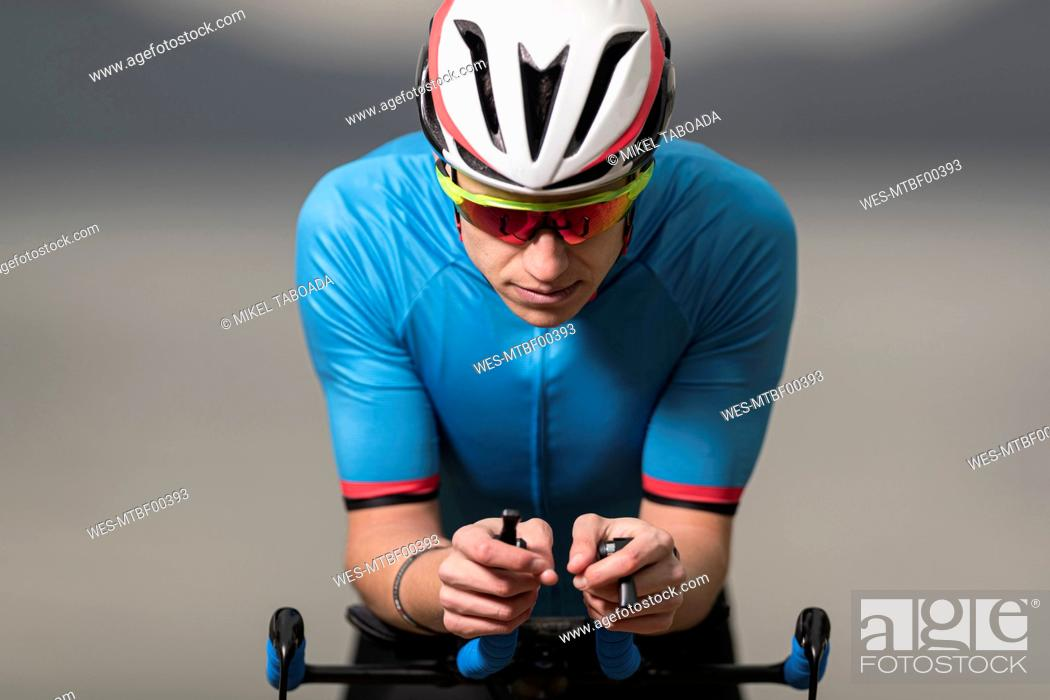Stock Photo: Young male athlete in sports clothing riding racing bicycle.