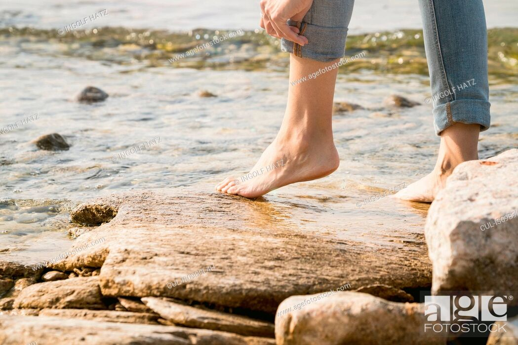 Stock Photo: Cropped view of woman barefoot on rocks.