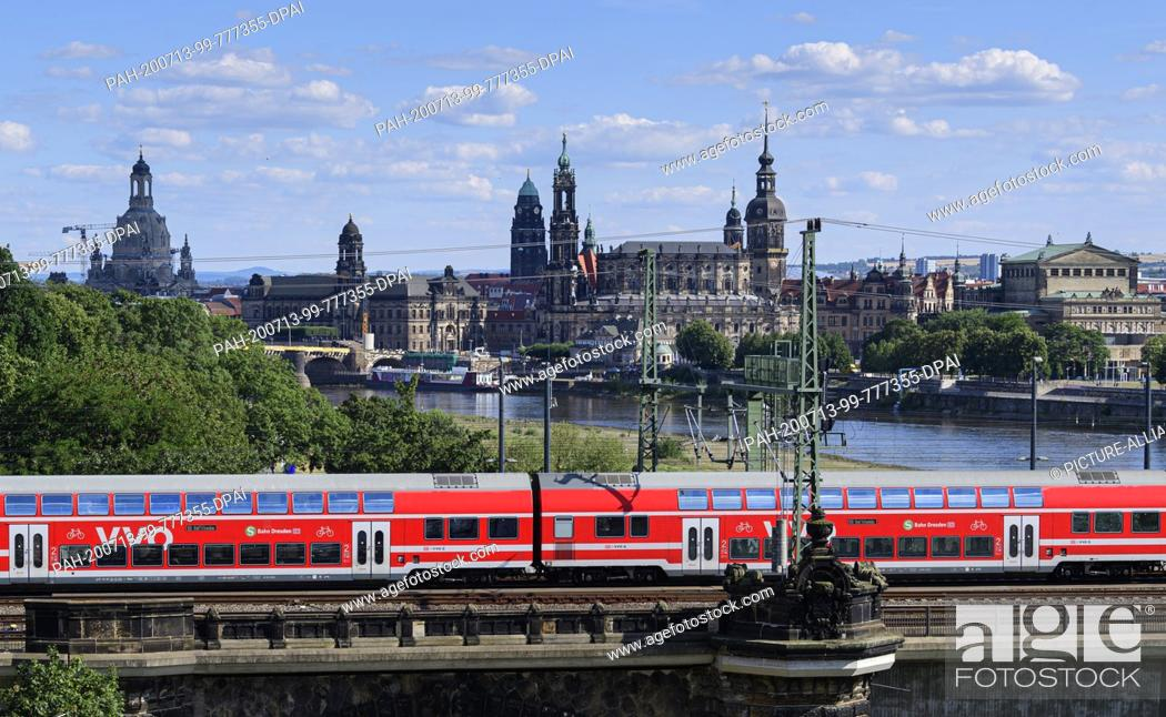 Stock Photo: 13 July 2020, Saxony, Dresden: A suburban train runs in front of the historic old town scenery with the Frauenkirche (l-r), the Ständehaus, the Hofkirche.