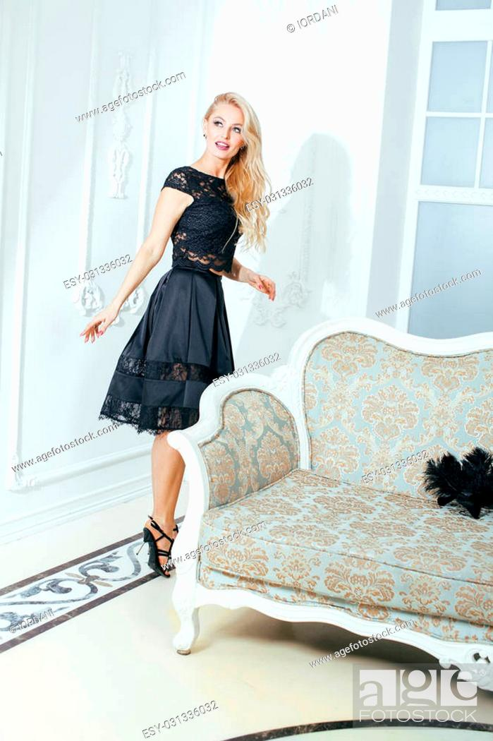 Imagen: stylish elegant blonde woman in beauty rich interior, wearing black dress smiling celebration.