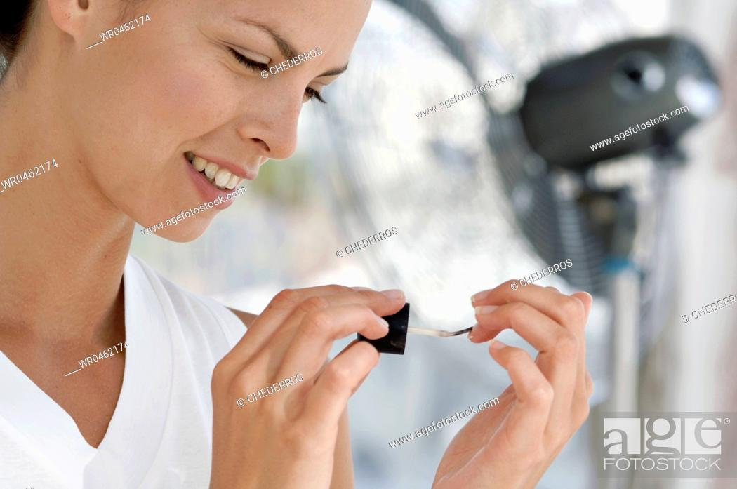 Imagen: Close-up of a young woman painting her fingernails.