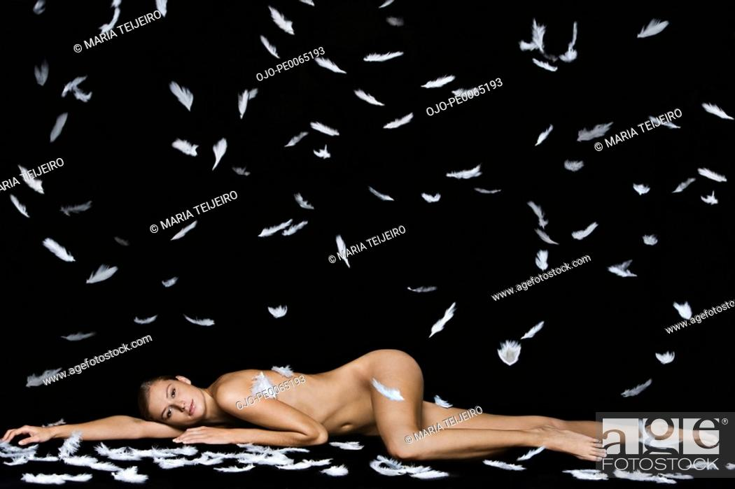 Stock Photo: Feathers falling on nude woman laying on floor.