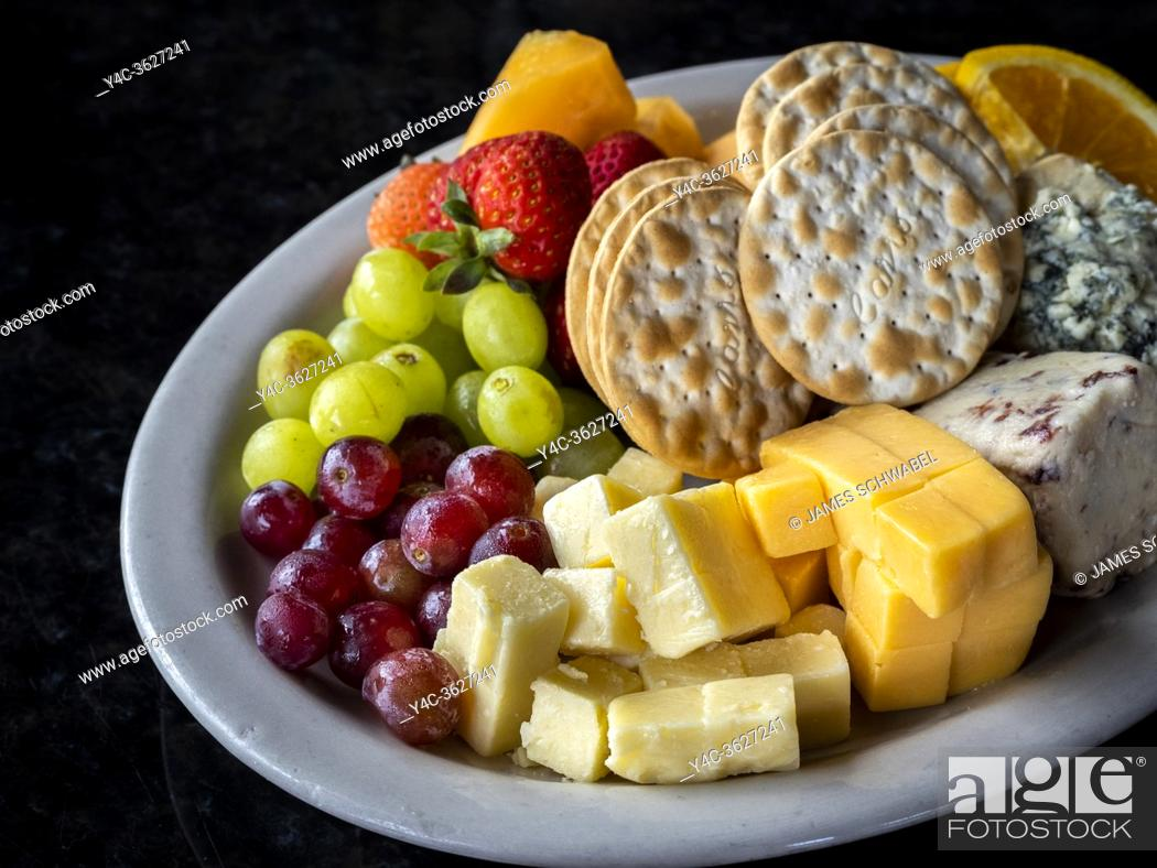 Imagen: Fruit cheese and crackers and a plate on a black background.
