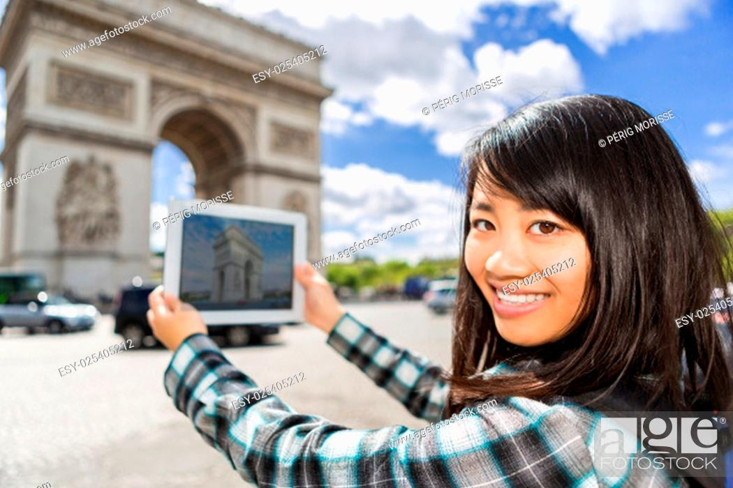Stock Photo: View of a Young attractive asian tourist taking pictures in Paris.