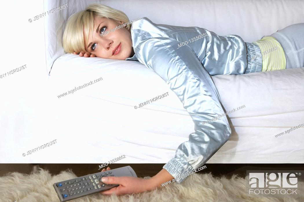 Stock Photo: Woman lying on sofa holding remote control.