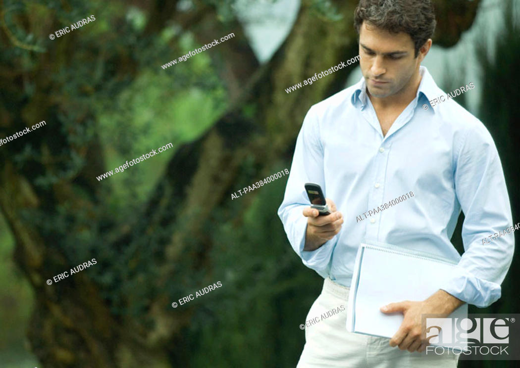 Stock Photo: Man using cell phone outdoors, holding documents.