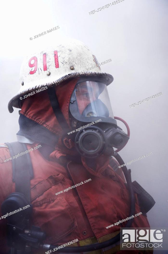 Stock Photo: fire fighter wearing oxygen mask.