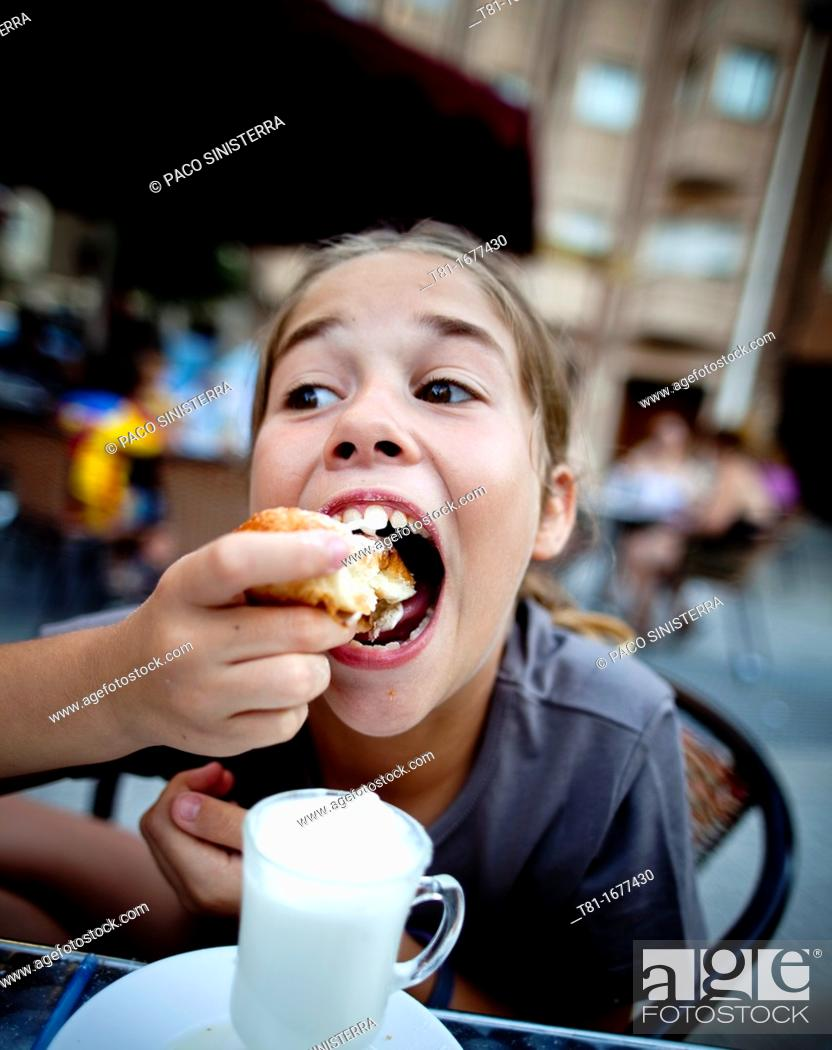 Stock Photo: Girl eating in an outdoor café.