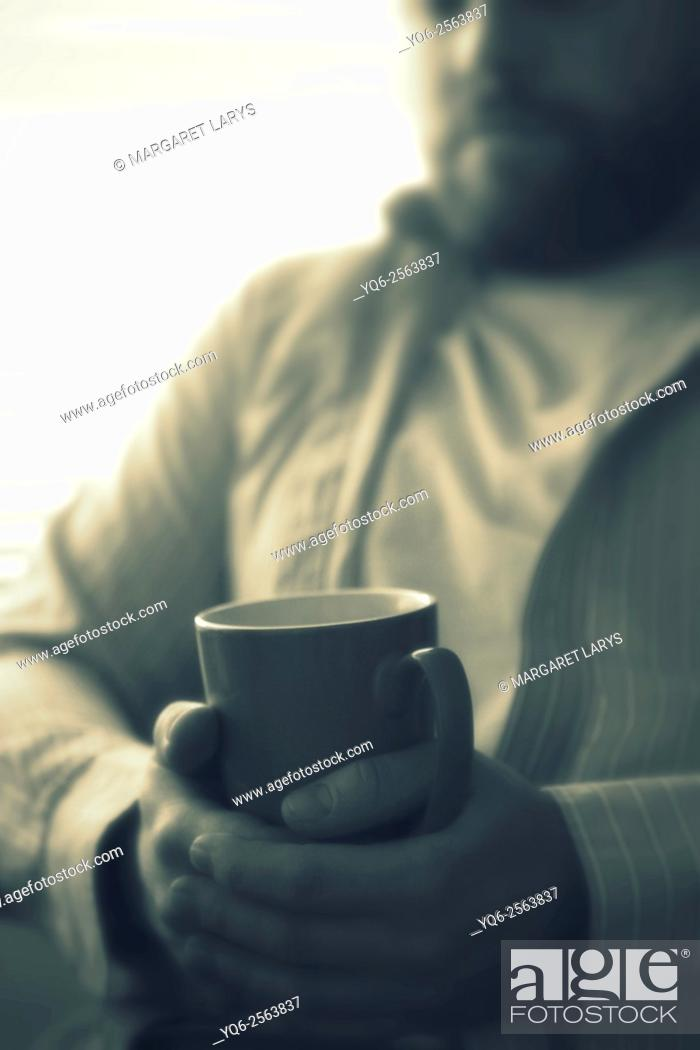 Stock Photo: Young man with a beard sitting in the chair and holding a cup of tea. His face is blurred and the focus is on hands and a cup.