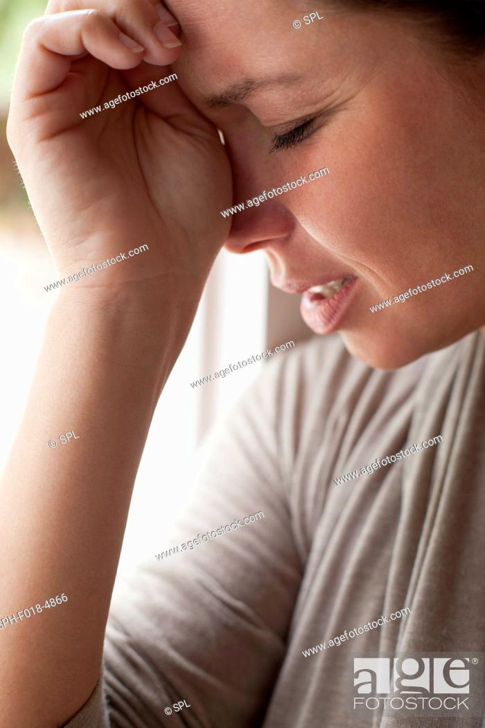 Stock Photo: Woman with hand on forehead.