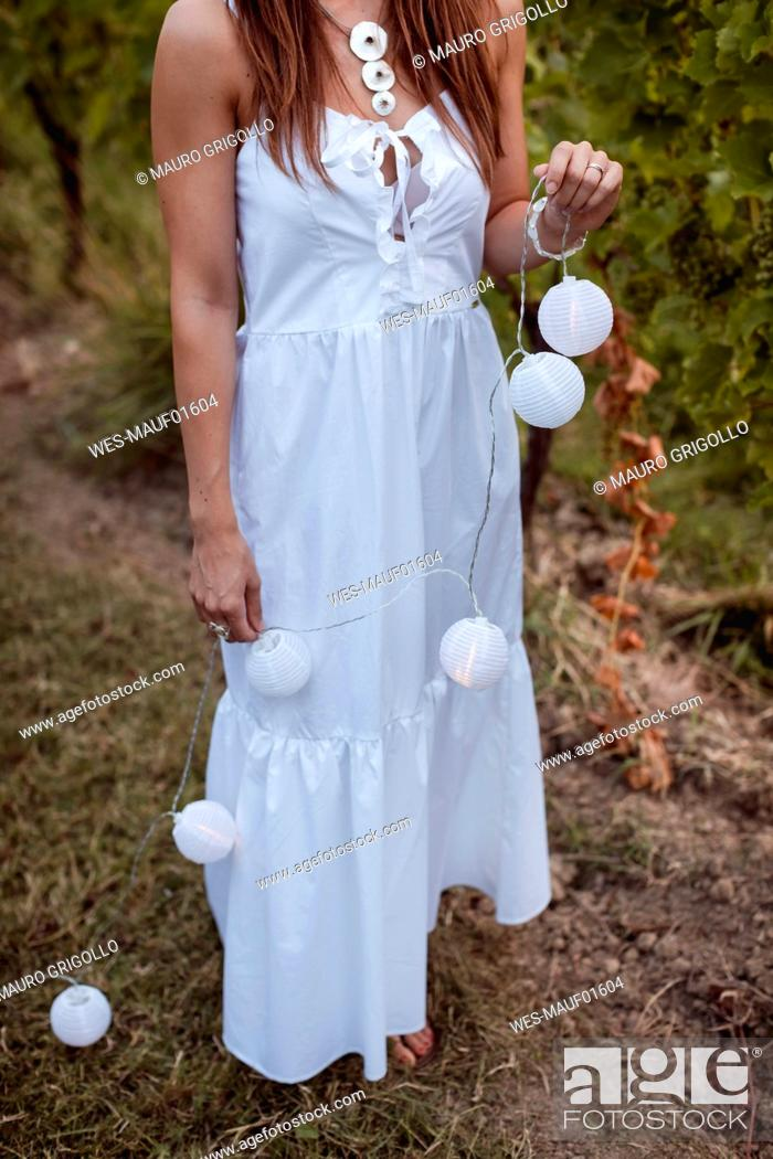 Stock Photo: Young woman decorating vineyard with fairy lights for a picnic.