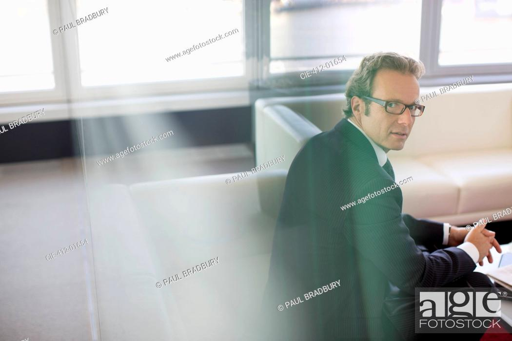 Stock Photo: Businessman sitting in office lobby area.