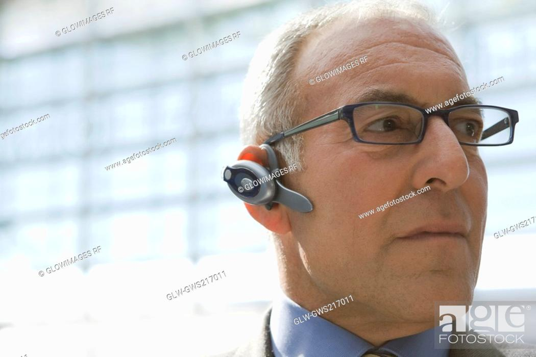 Stock Photo: Close-up of a businessman wearing a bluetooth and looking away.