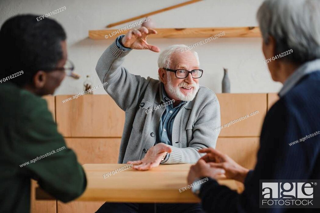 Stock Photo: group of multiethnic senior friends sharing stories from past.